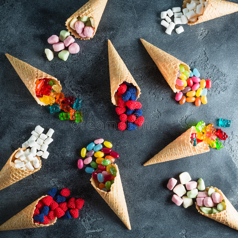 Pattern of colorful bright assorted candy in waffle cones on dark background. Flat lay, top view stock image