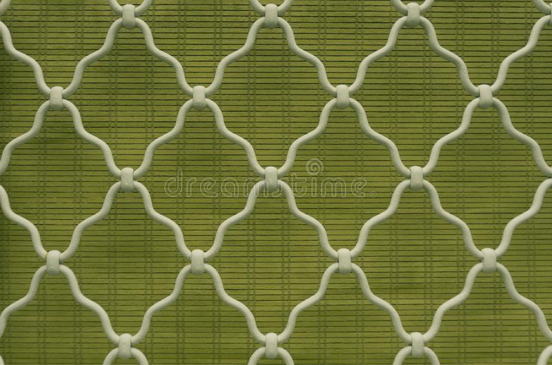Pattern of diamond shape on white curved wrought iron steel on the lattice window, green bamboo curtain background, vintage style. Lattice work for house royalty free stock photos