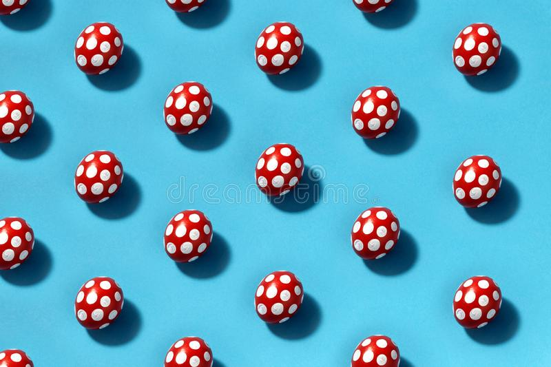 Pattern of Easter eggs in red with white spots on a blue background. Creative concept royalty free stock photography