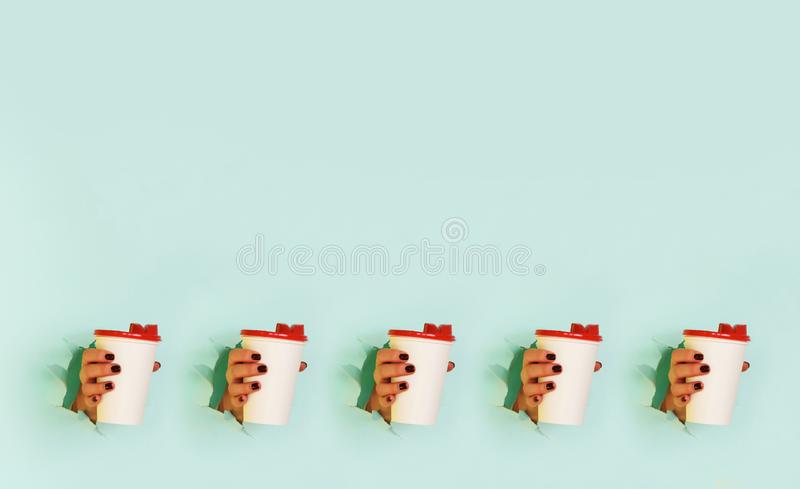Pattern of female hand holding white paper mug on blue background. Take away coffee cup concept. Mock up with copy space stock photography