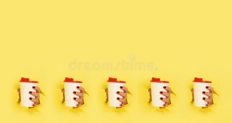 Pattern of female hand holding white paper mug on yellow background. Take away coffee cup concept. Mock up with copy space stock image