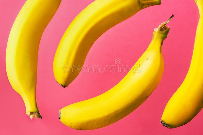 Pattern from floating flying in the air yellow bananas on fuchsia pink background. Tropical fruits vitamins healthy vegan diet royalty free stock images