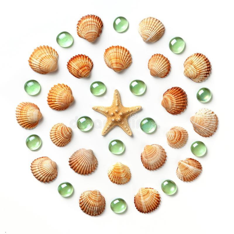 Pattern in the form of a circle made of shells, starfish and green glass beads isolated on white background. Flat lay, top view royalty free stock photography