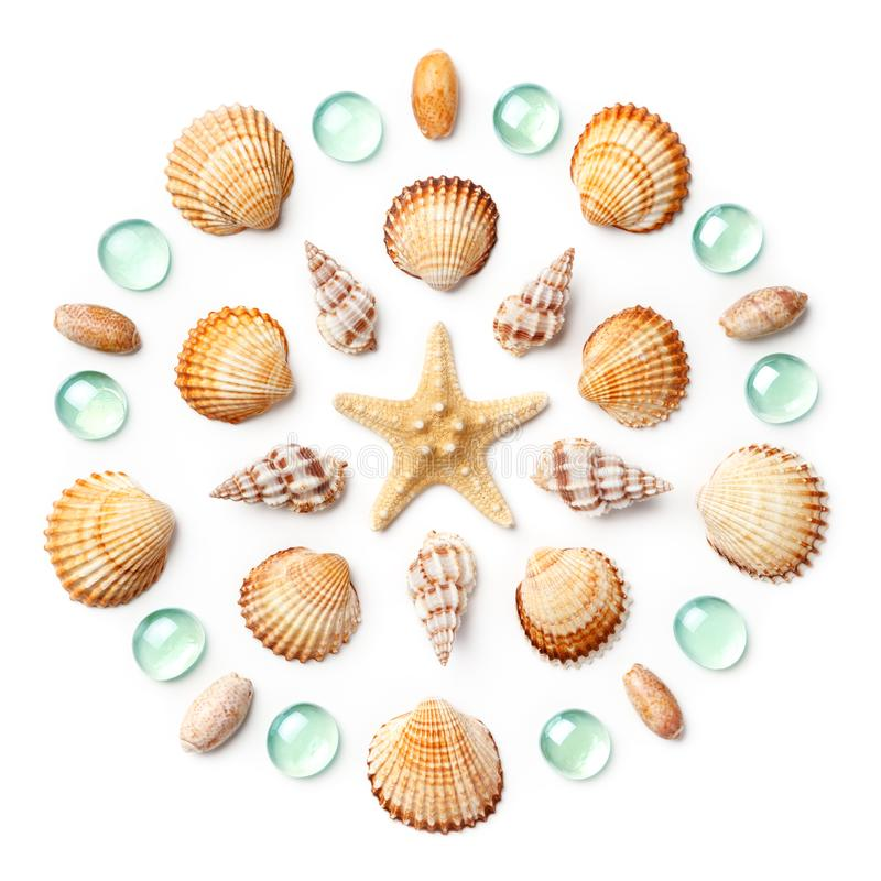 Pattern in the form of a circle made of shells, starfish and green glass beads isolated on white background. Flat lay, top view stock photos