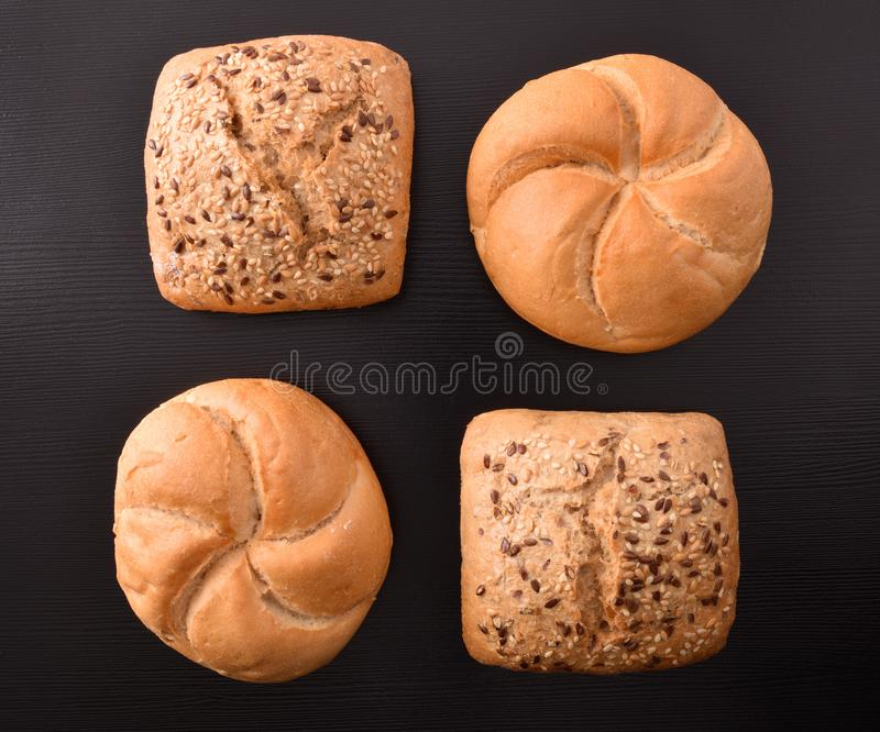 Pattern of four loaves on black wooden table top. View. Horizontal composition stock image