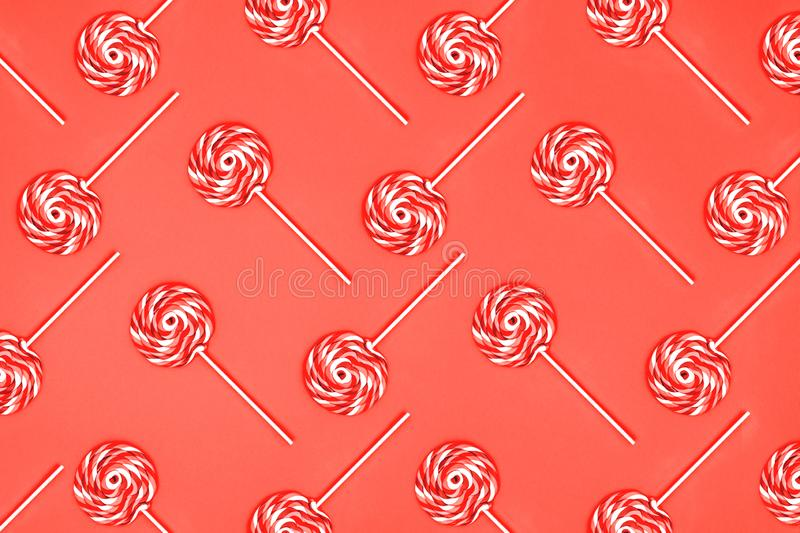 Pattern of giant lollipops on solid background . Living coral theme - color of the year 2019. Horizontal stock photo