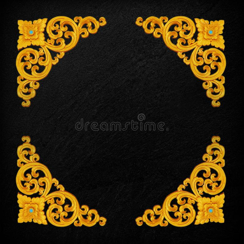 Pattern of gold Stucco flower on a black stone. stock photo