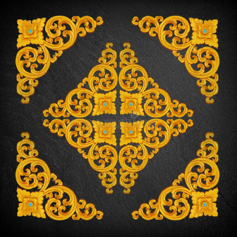 Pattern of gold Stucco flower on a black stone. royalty free stock photo