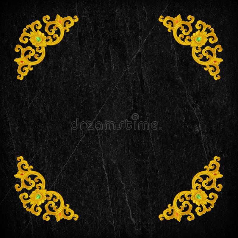 Pattern of gold Stucco flower on black stone. royalty free stock photo