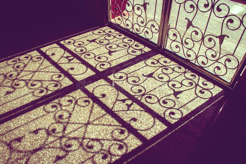 Pattern of light and shadow on floor from asian style bending steel door royalty free stock photo