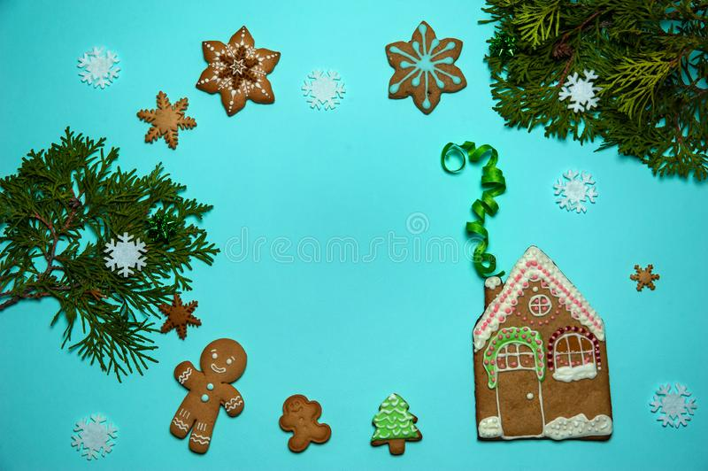 The pattern is made of branches of thuja, white snowflakes and homemade glazed gingerbread in the form of a house, a man, a star a stock image