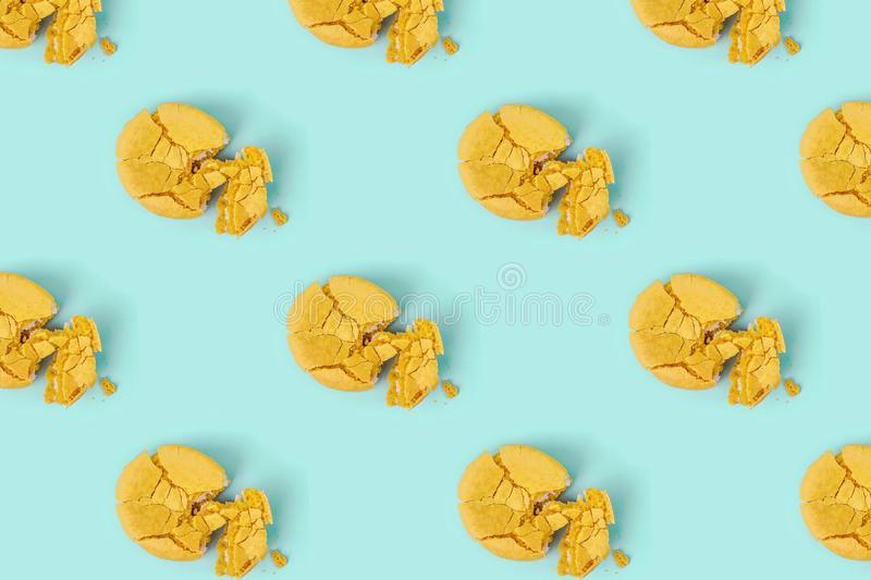 Pattern made of crushed yellow macaroons on pastel blue background. Creative layout. royalty free stock photo