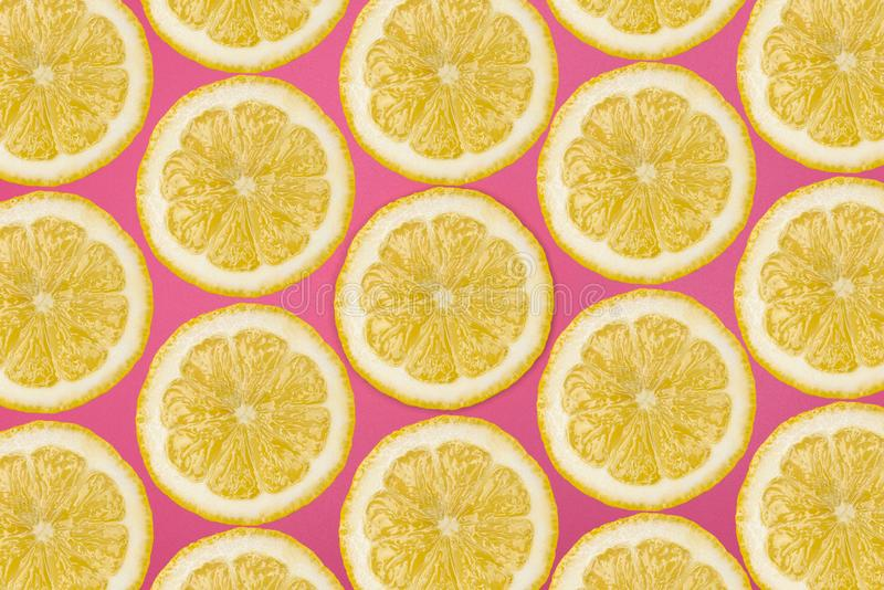 Pattern made from fresh lemon slices on a pink background, overhead view, flatlay. Fruit background. royalty free stock image
