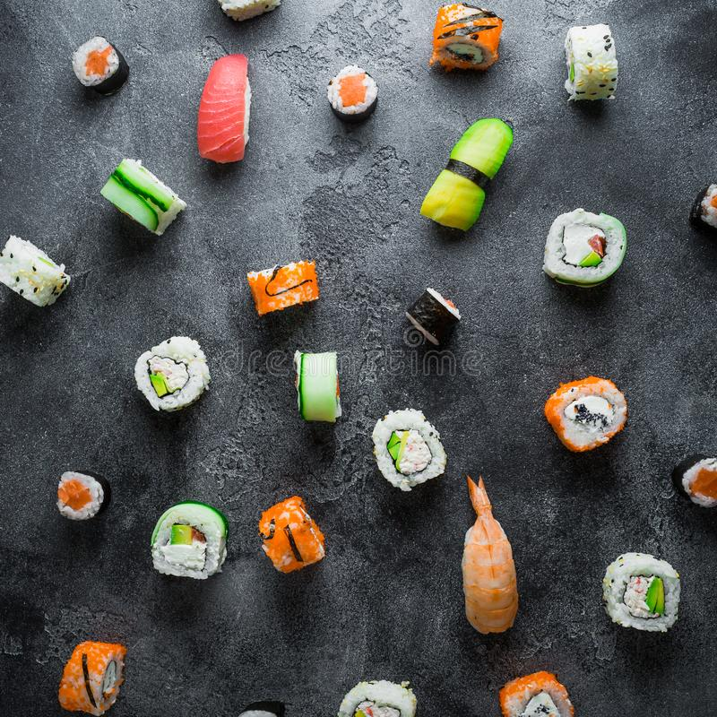 Pattern made of raw sushi rolls on a dark background. Japanese food. Flat lay. Top view stock photos