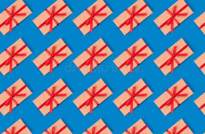 Pattern made of simple gift box decorated with red bow ribbon pattern on cyan blue background. Flat lay. Pattern made of  simple gift box decorated with red bow royalty free stock images