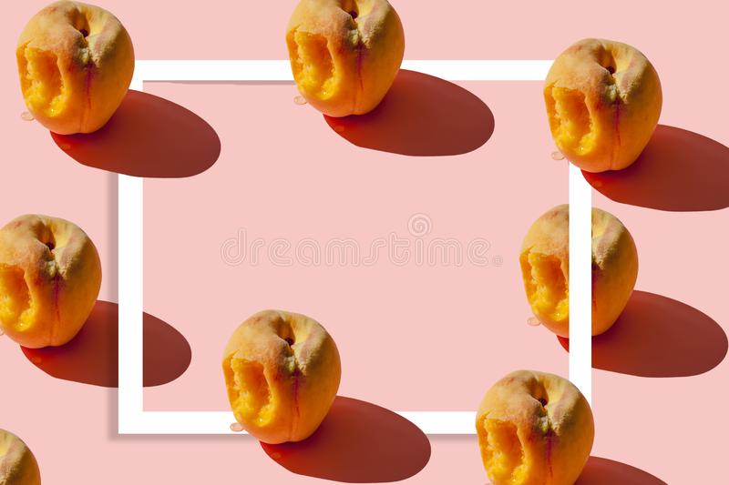 Pattern of many juicy ripe peaches on a pastel pink background with a white frame in the center for your text. Creative layout.  stock photo