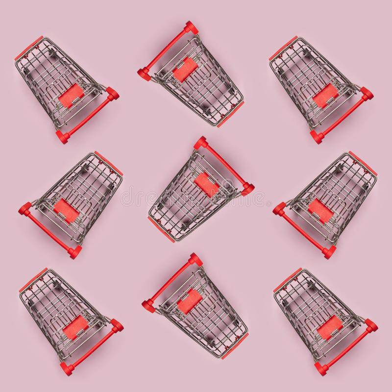 Pattern of many small shopping carts. Minimalism flat lay top view royalty free stock images