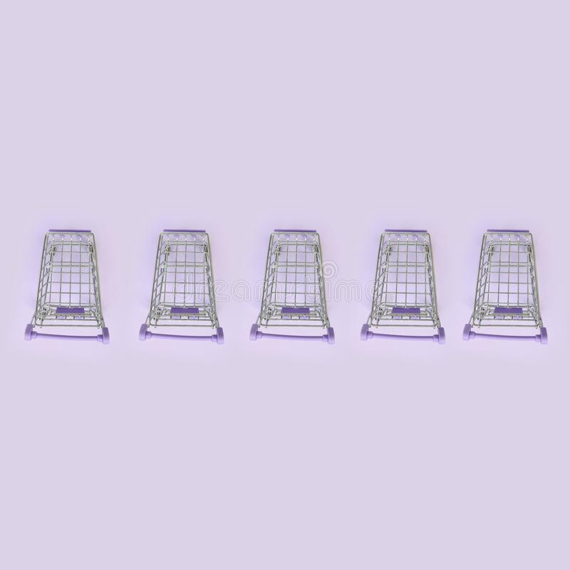 Pattern of many small shopping carts on a violet background. Minimalism flat lay top view royalty free stock photography