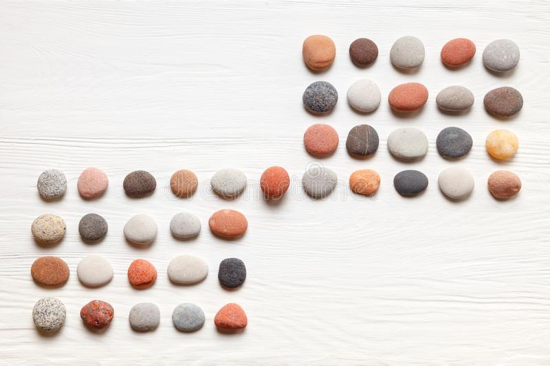Pattern of natural multicolored pebbles on white wooden background. Spa decoration. Meditation and relaxation concept. Flat lay, top view. Copy space royalty free stock photo