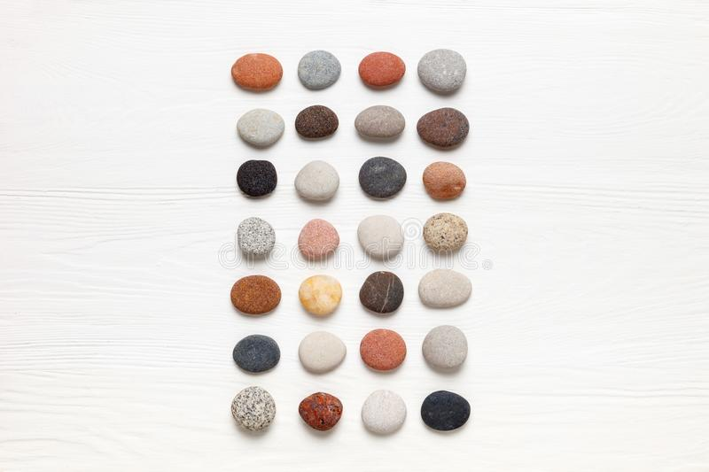 Pattern of natural multicolored pebbles on white wooden background. Spa decoration. Meditation and relaxation concept. Flat lay, top view. Copy space royalty free stock photos