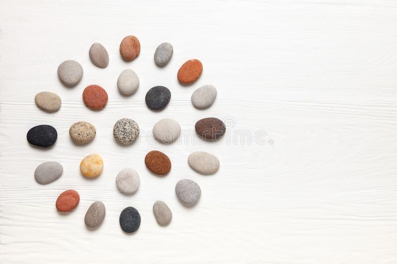 Pattern of natural multicolored pebbles on white wooden background. Spa decoration. Meditation and relaxation concept. Flat lay, top view. Copy space stock image