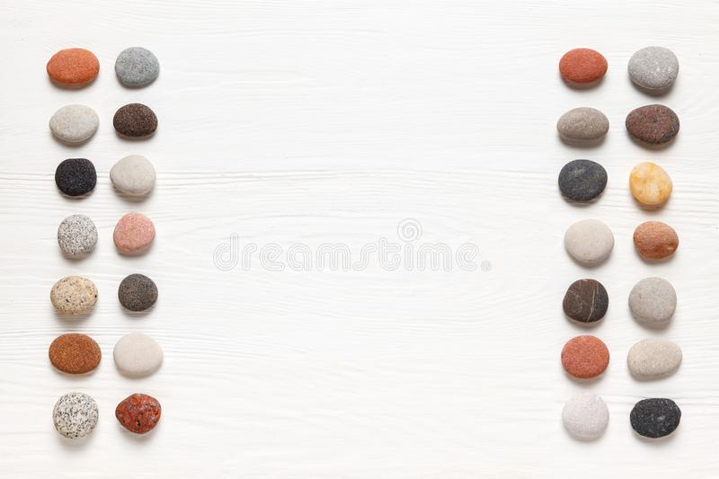 Pattern of natural multicolored pebbles on white wooden background. Spa decoration. Meditation and relaxation concept. Flat lay, top view. Copy space royalty free stock photography