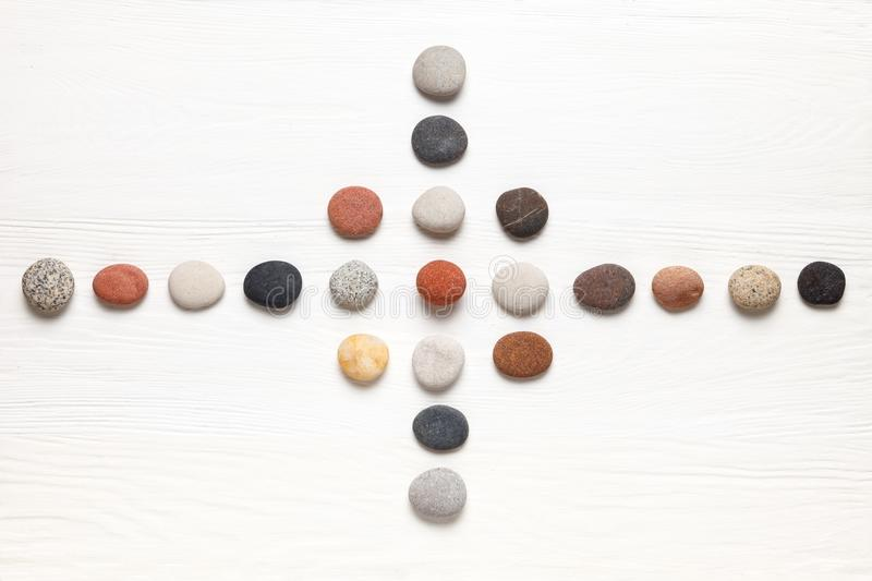 Pattern of natural multicolored pebbles on white wooden background. Spa decoration. Meditation and relaxation concept. Flat lay, top view. Copy space royalty free stock images