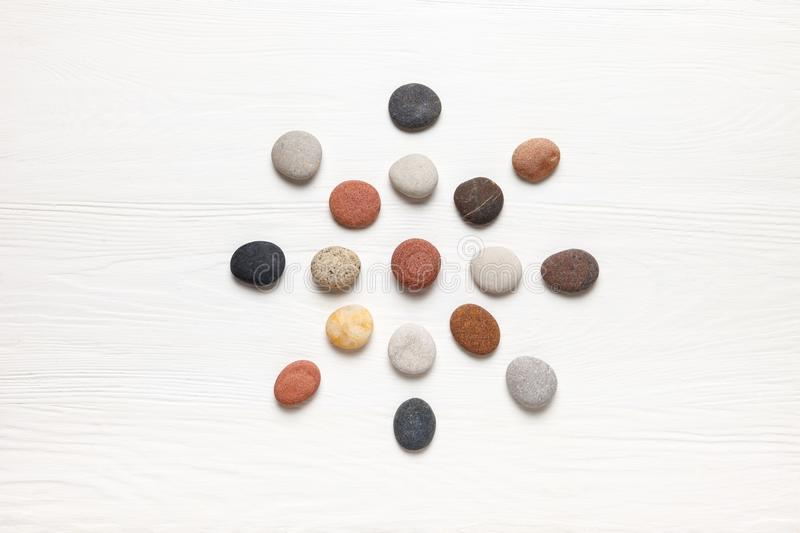 Pattern of natural multicolored pebbles on white wooden background. Spa decoration. Meditation and relaxation concept. Flat lay, top view stock image