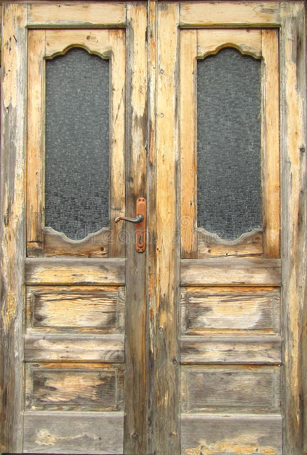 Pattern of old wooden double door with glass panes outside exposed to the weather. Close-up stock photos
