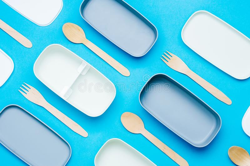Llunch boxes with wooden forks and spoons on blue background stock images