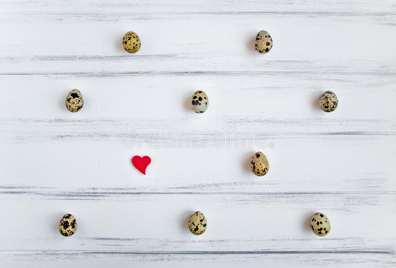 Pattern with quail eggs on white wooden vintage table. Flat lay, top view stock photo