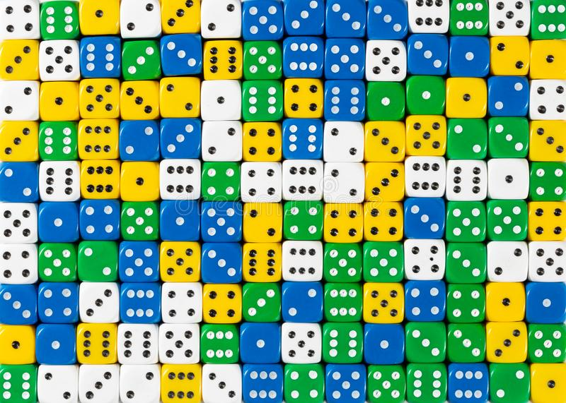 Pattern of random ordered white, yellow, green and blue dices. Pattern background of random ordered white, yellow, green and blue dices royalty free stock image