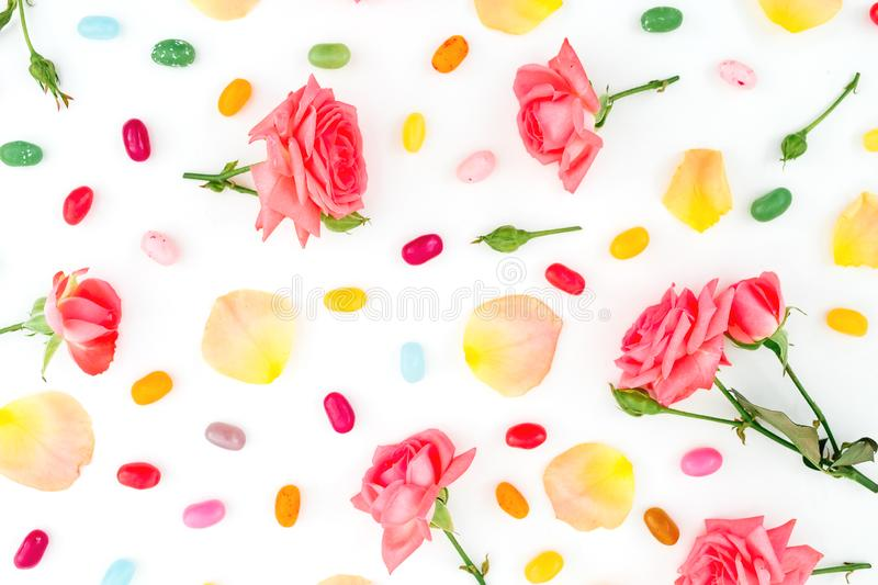 Pattern of roses flowers and petals with bright sugar candy on white background. Flat lay, top view. Pattern of roses flowers and petals with bright sugar candy stock photos