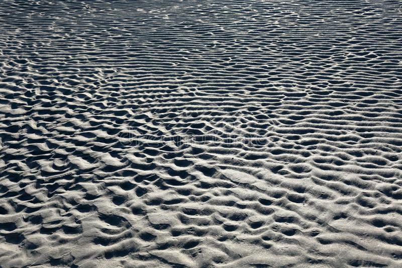 Pattern in the sand on a beach. Pattern in the sand formed by waves and wind stock image