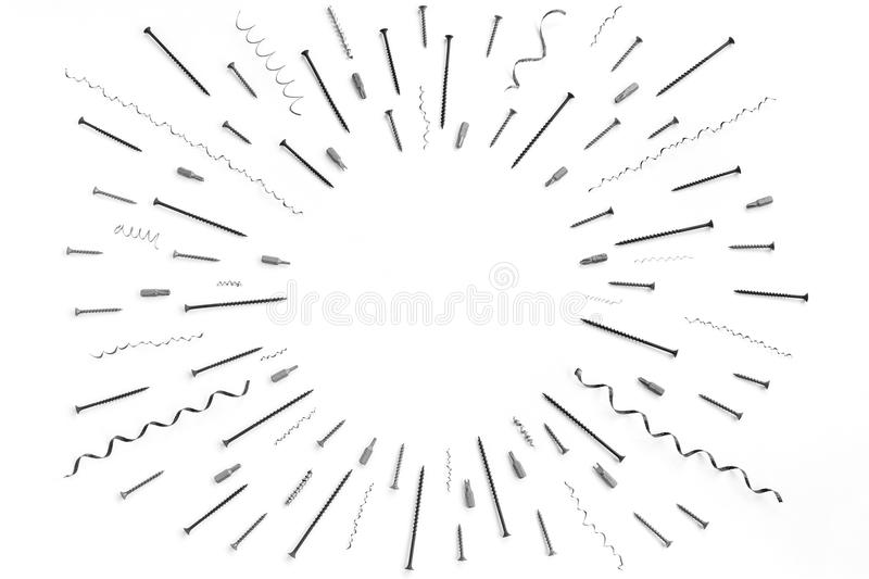 Pattern of screws, nails, metal shavings, bits for a screwdriver with circle place for text. In the middle royalty free stock photography