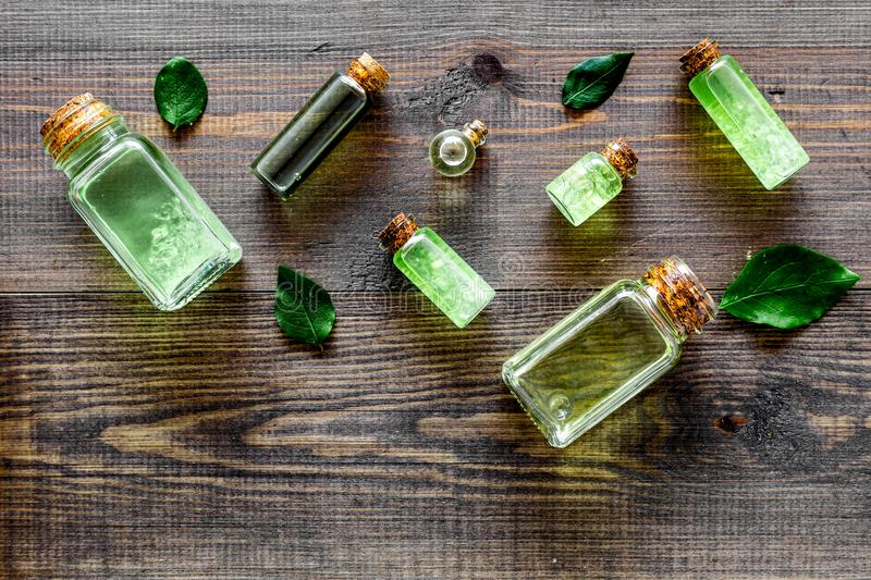 Skin care products with tea tree oil in bottles on dark wooden background top view pattern copyspace royalty free stock photography