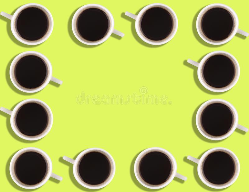 A pattern of small coffee cups on a bright colored background with copyspace.  royalty free stock image