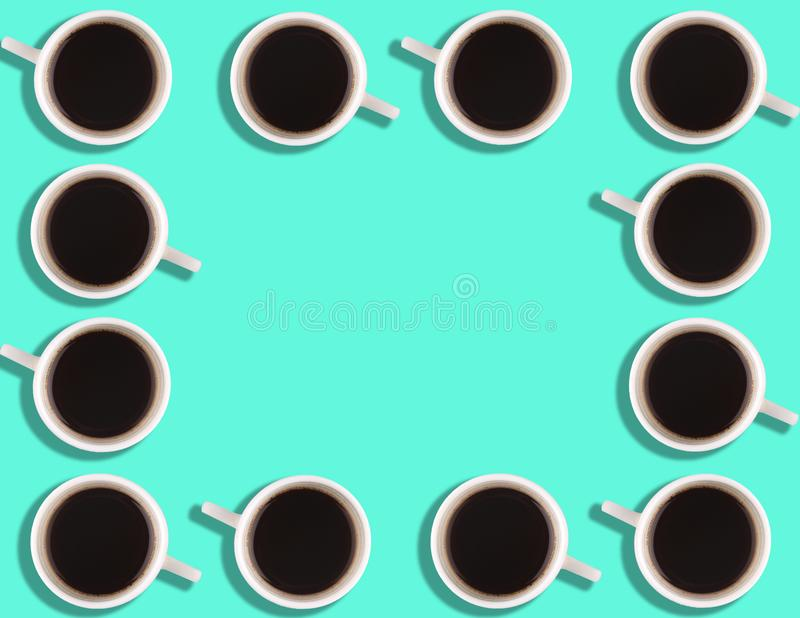 A pattern of small coffee cups on a bright colored background with copyspace.  stock photos