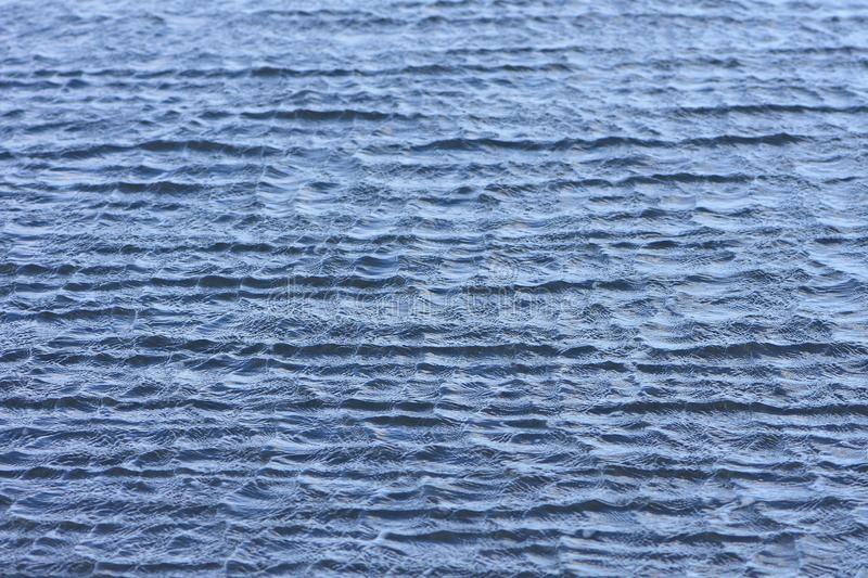 Water surface with tiny waves. Pattern of steel blue sea surface with tiny choppy irregular waves stock image
