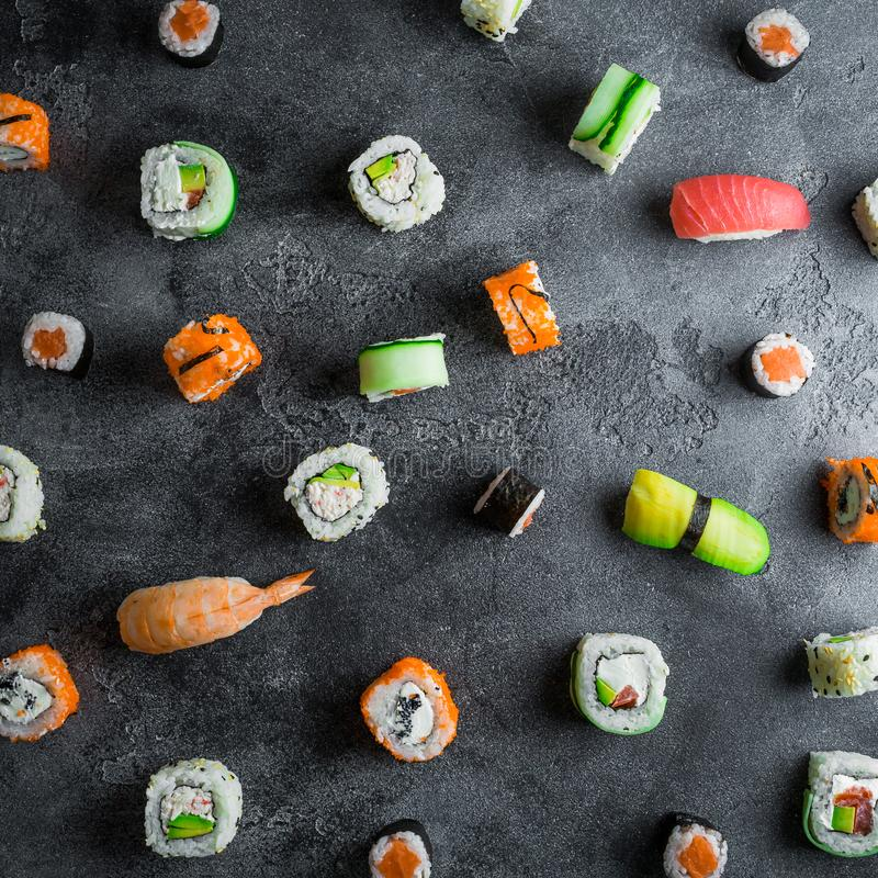 Pattern with sushi rolls on dark background. Japanese food. Flat lay. Top view royalty free stock images