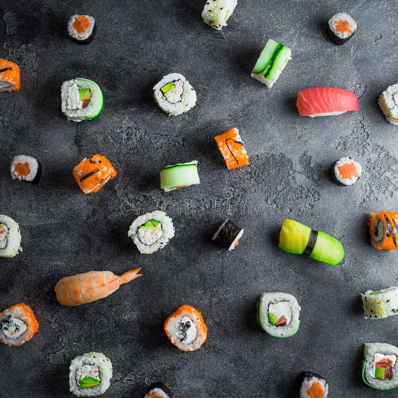 Pattern of sushi rolls on a dark background. Japanese food. Flat lay. Top view royalty free stock photo