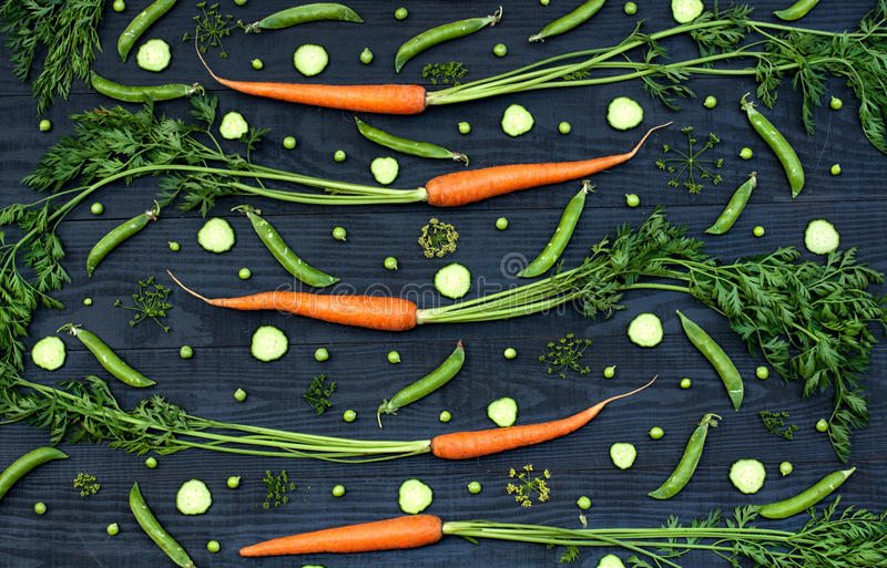 Pattern from vegetables on a black wooden background stock image