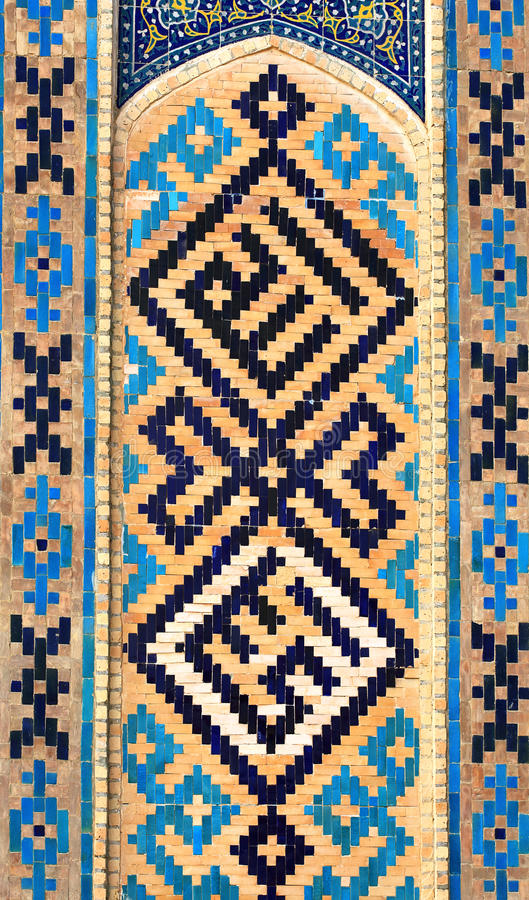 Pattern on the wall. Black, blue and yellow ornament on the oriental buildings wall stock photos
