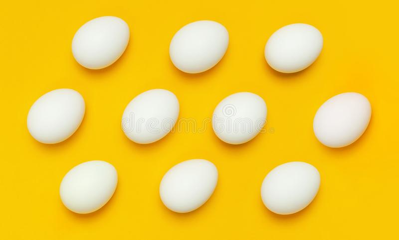 Pattern from White chicken eggs on yellow background top view flat lay copy space. Creative food minimalistic background, Easter. royalty free stock photos