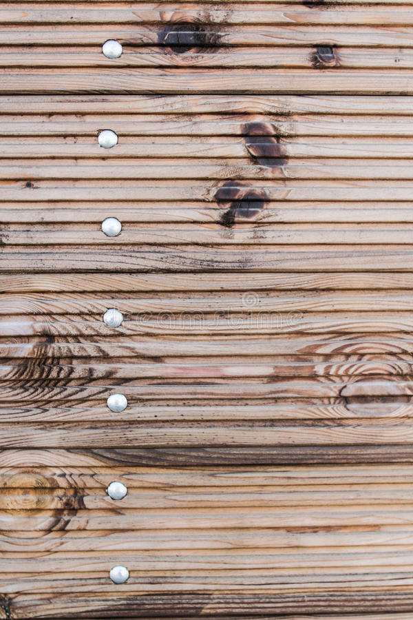 Pattern: yellow new wooden fence. Natural wood, with horizontal stripes, white - yellow color showing steel step bolts stock photos