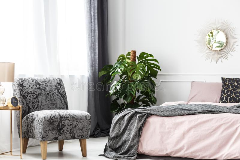 Patterned armchair in cozy bedroom stock photos