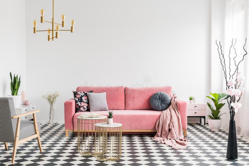 Patterned armchair near gold tables and pink sofa in white flat interior with plants. Real photo. Concept stock photography