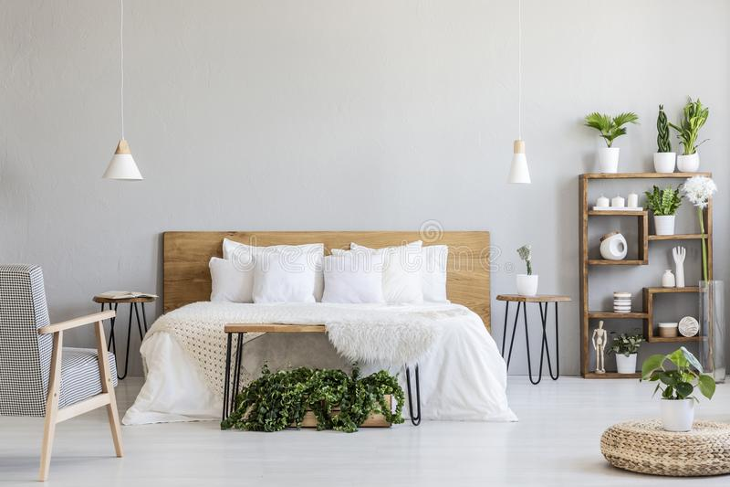 Patterned armchair near white wooden bed in grey bedroom interior with pouf and plants. Real photo royalty free stock image