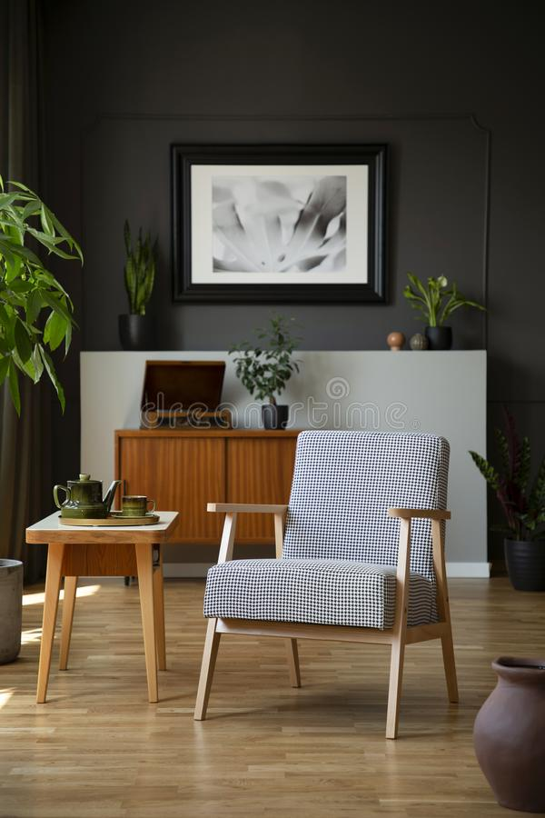 Patterned armchair next to wooden table in dark grey living room interior with poster. Real photo stock photos