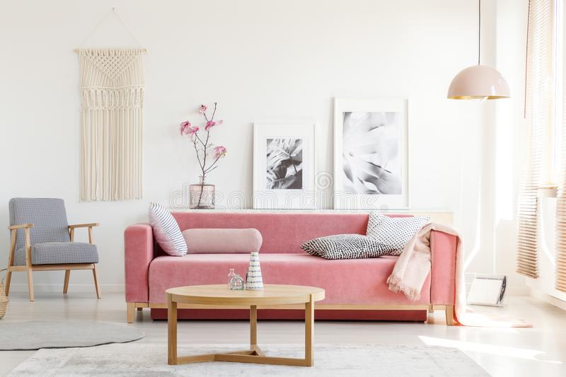 Patterned armchair and pink couch in feminist apartment interior. With flowers and posters. Real photo stock photo